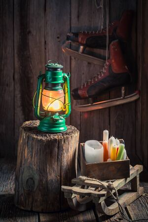 Vintage wooden winter cottage with snow and oil lamp
