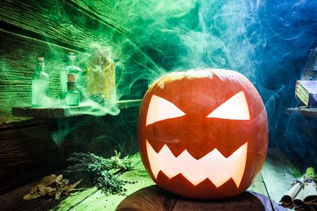 Glühender Kürbis für Halloween auf Holzschreibtisch