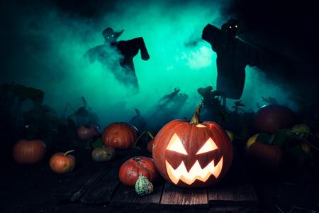 Enge pompoen met groene mist en vogelverschrikkers voor Halloween Stockfoto