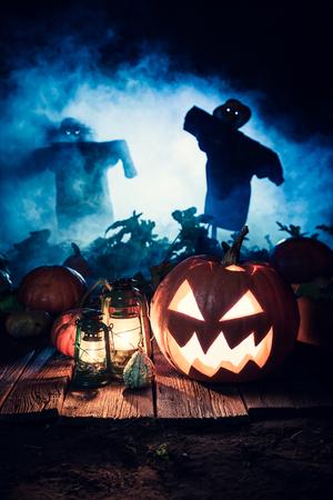 Enge Halloween-pompoen met blauwe mist en vogelverschrikkers