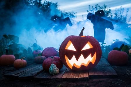 Griezelige pompoen met vogelverschrikkers op het gebied voor Halloween