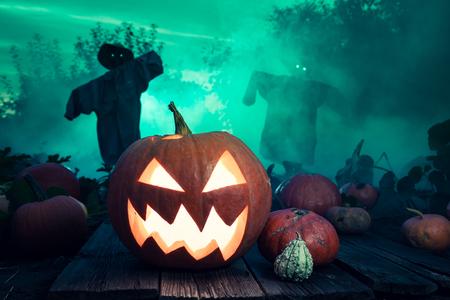 Gloeiende Halloween-pompoen met groene mist en vogelverschrikkers