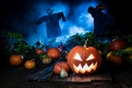 Oranje pompoen met blauwe mist en vogelverschrikkers voor Halloween Stockfoto