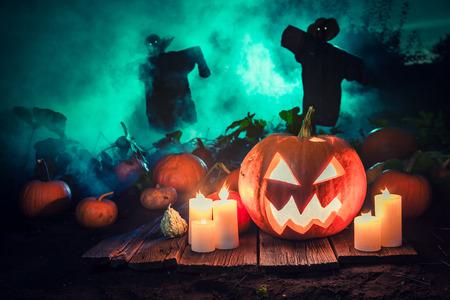 Griezelige pompoen met groene mist en vogelverschrikkers voor Halloween Stockfoto