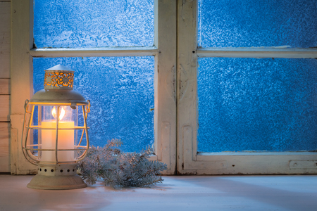 Blue window at night with burning candle for Christmas