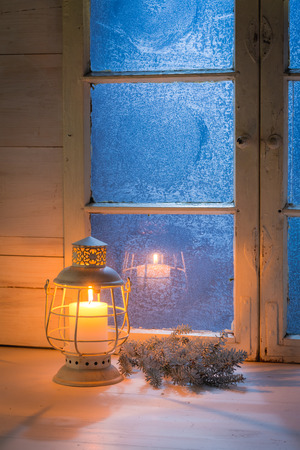 Frosted blue window and burning candle for Christmas Stock Photo