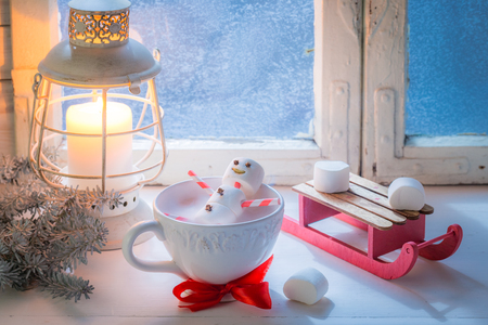 Relaxing in hot cocoa snowman made of marshmallows for Christmas