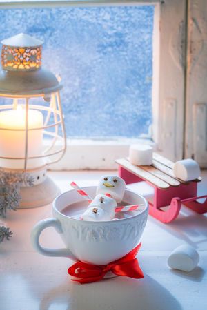 Relaxing in hot cocoa snowman for Christmas by frozen window Stock Photo