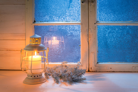 Blue window at night and burning candle for Christmas