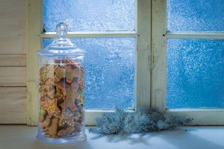 Cold blue window with cookies in jar for Christmas