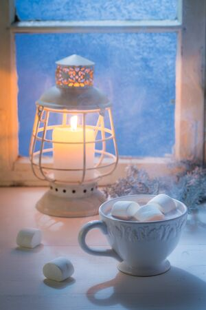 Christmas chocolate with marshmallows in cold evening by blue window Stock Photo