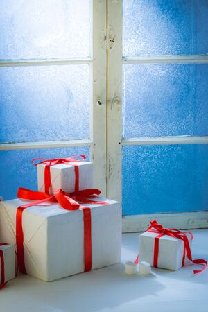 Gifts for Christmas and frozen window at cold night Stock Photo