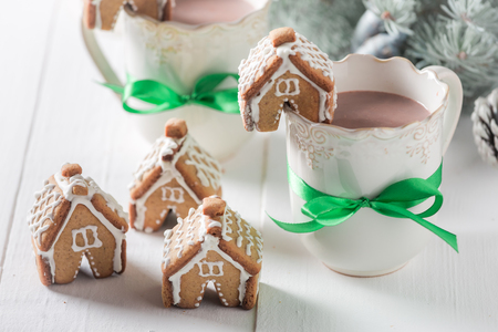 Cute gingerbread cottages with sweet drink in Christmas winter evening Stock Photo