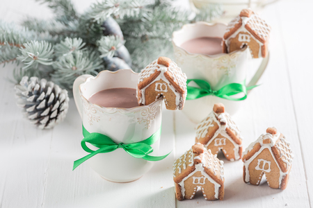 Small gingerbread cottages with tasty cocoa as Christmas snack