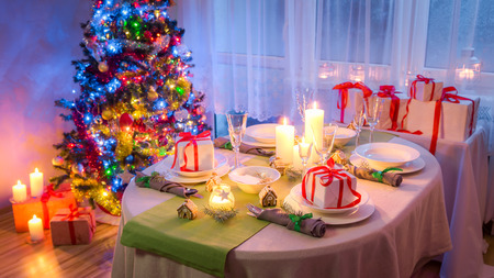 Family Christmas table setting with green and white decoration Stock Photo