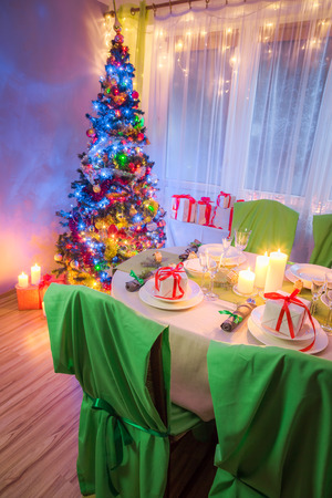 Christmas table setting with present and tree in frosty evening