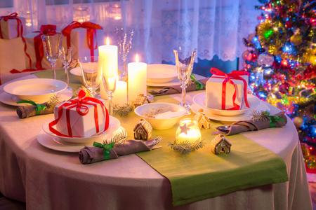 凍るような冬の夜の間に家族のクリスマス テーブルの設定