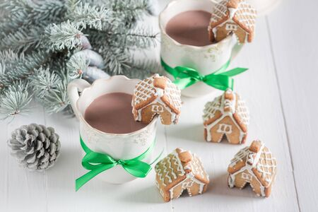 Aromatic gingerbread cottages with hot chocolate for Christmas
