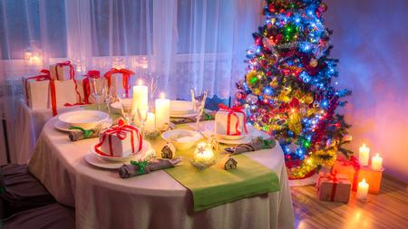 冷ややかな冬の夜の間にゴージャスなクリスマステーブルの設定