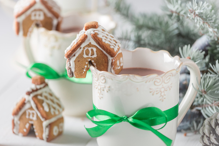 Aromatic gingerbread cottages with hot chocolate as Christmas snack Stock Photo