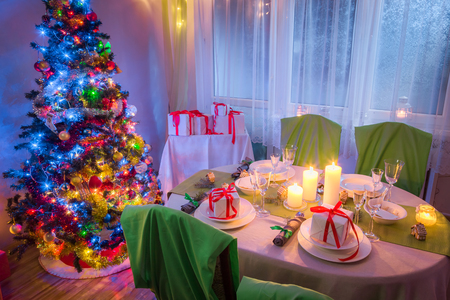Beautiful Christmas table setting with Christmas tree and gifts Stock Photo