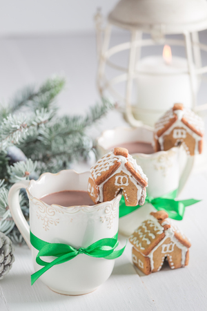 Homemade gingerbread cottages with hot chocolate in Christmas winter evening