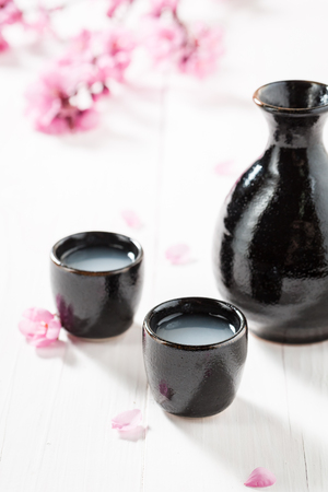 Unfiltered white sake sake with flowers of blooming cherry Foto de archivo