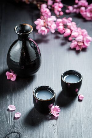Unfiltered white sake sake with blooming flowers