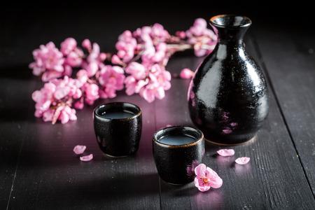 Ongefilterde witte sake sake op zwarte tafel