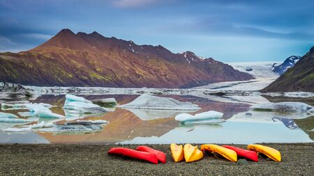 Kayaks at glacial lake in the cold mountains, Iceland