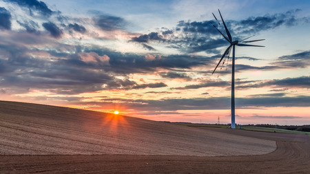Beautiful sunset at countryside with wind turbine in autumn Stock Photo