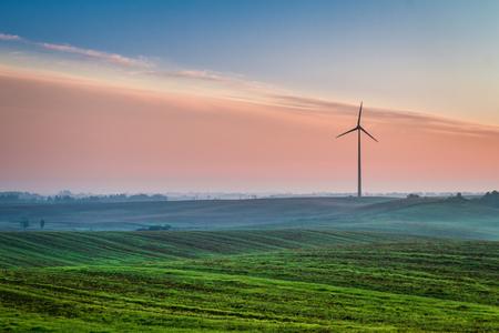 Beautiful sunrise at countryside with wind turbine