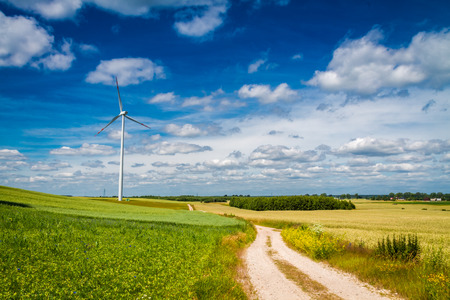 White wind turbines on green field as alternative energy