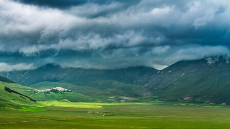 Dramatic sky and valley in Castelluccio at summer, Umbria, Italy Stock Photo - 87983887