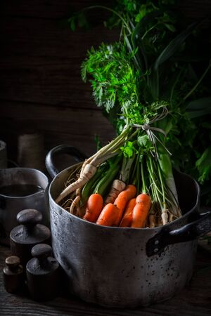 Preparation for homemade vegan soup with carrots, parsley and leek