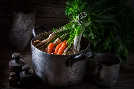 Ingredients for homemade vegan soup with carrots, parsley and leek