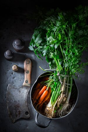 Preparation for tasty vegan soup with carrots, parsley and leek