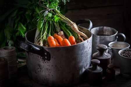 Preparation for homemade broth with carrots, parsley and leek
