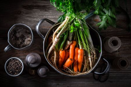 Ingredients for tasty broth with carrots, parsley and leek Фото со стока