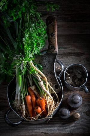 Ingredients for healthy vegan soup with carrots, parsley and leek