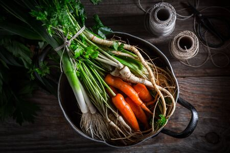 Ingredients for tasty vegan soup with carrots, parsley and leek