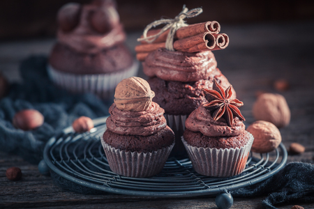 Tasty chocolate cupcake with nuts and brown cream