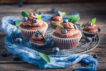 Tasty chocolate muffin with fresh blueberries and cream