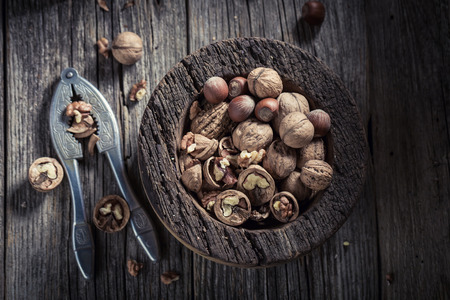 Tasty walnuts and hazelnuts with on rustic table Stock Photo