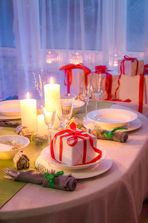 Family Christmas table setting with white decoration in evening