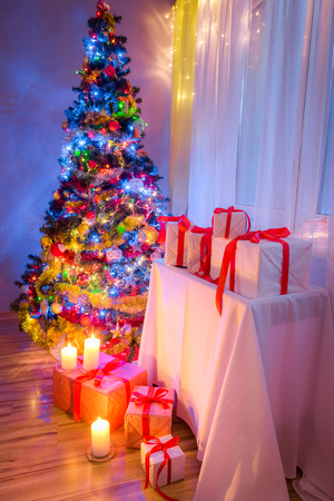 Traditionally Christmas tree with gifts for Christmas in evening Stock Photo