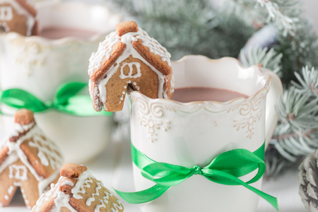 Cute gingerbread cottages with hot chocolate in Christmas evening