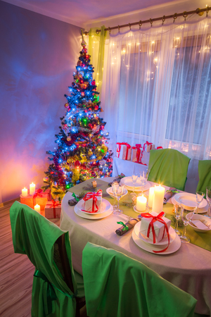 Christmas table setting with present and tree in evening