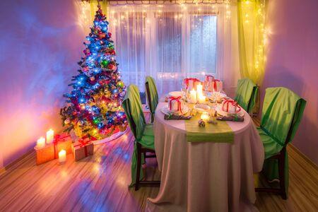 凍るような冬の夜の間にクリスマスのテーブルの設定