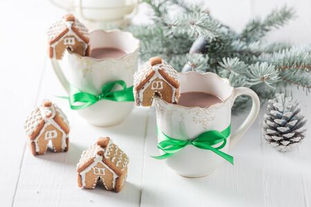Cute gingerbread cottages with tasty cocoa in Christmas